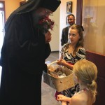 Young ladies meet Bishop Alexander at the doors of the church with flowers