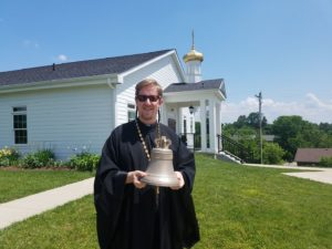 Fr. Justin Patterson holding one of our new bells to be blessed on All-Saints Sunday, 2018